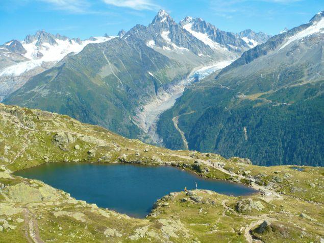 Po lewej stronie w tle – Glacier du Tour. W tle po środku – Glacier d'Argentière. Lodowiec ten ma swoje źródło na około 3 000 m, wśród szczytów granicznych Francji i Szwajcarii -> Mont Dolent – 3 823 m i Aiguille de Triolet – 3 730 m. Niżej, w stronę doliny znajdują się trzy szczyty sięgające powyżej 4 000 m n.p.m. -> Les Droites – 4 000 m, La Grande Rocheuse – 4 102 m i Aiguille Verte – 4 122 m.