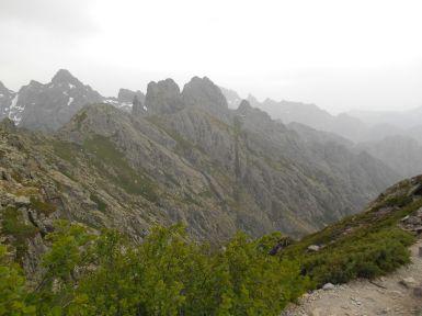 Po przejściu na zachodnie zbocze masywu Muvrella widok rozpościera się na dolinę Falasorma. Przełęcz Bocca di a Muvrella to granica między regionem Górnej Korsyki (Haute-Corse) – Balagne i dolina Falasorma. Chmury zasłaniają niestety widok na zatokę Porto oraz rezerwat Scandola.