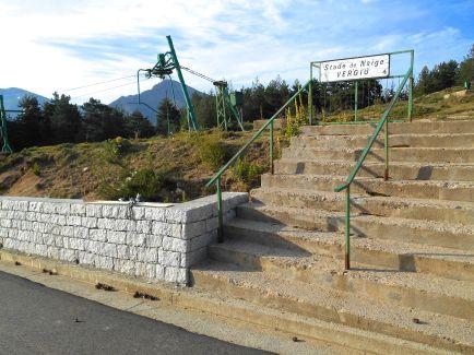 Szlak przechodzi w pobliżu przełęczy Col de Verghio i po krótkim odcinku na drodze asfaltowej dochodzę do stacji narciarskiej Le Castel de Vergio (1404 m). Przechodząc obok hotelu i pola biwakowego zauważam parę Francuzów, z którymi spotykałem się na poprzednich etapach. Mieszkają oni pół roku w okolicach Ajaccio, otrzymałem od nich kilka ciekawych informacji dotyczących szlaku GR20. Oni tez mnie zauważają i wychodzą mi na powitanie. Rozmawiamy przez chwile, dowiaduje się od nich, ze na popołudnie przewidywane są opady deszczu i burze i ze oni decydują zatrzymać się na tym etapie (sami już wiele razy przechodzili etapy GR20). Zegnamy się uściskiem dłoni i decyduje się na zwlekać, gdyż czeka mnie jeszcze parę godzin marszu przed dojściem do schroniska Manganu.